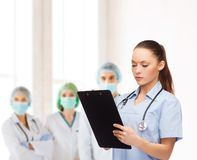Serious female doctor or nurse with stethoscope stock image