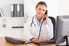 Serious female doctor on the phone. In her office Royalty Free Stock Photography