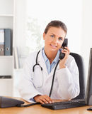 Serious female doctor on the phone Stock Photos