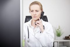 Serious Female Doctor on Phone Looking at Monitor Stock Photography