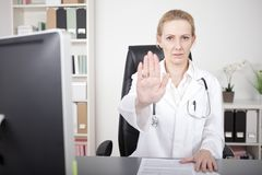 Serious Female Doctor Showing Stop Hand Pose Royalty Free Stock Images