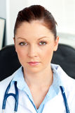 Serious female doctor smiling at the camera Stock Photography