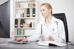 Serious Female Doctor Using her Desktop Computer Royalty Free Stock Image