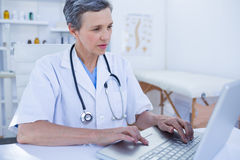 Serious female doctor using her laptop computer Stock Photography