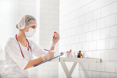 Serious female doctor writing blood-test result Stock Photography