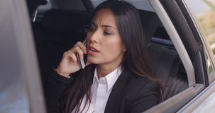 Serious female executive on phone in limousine stock video footage