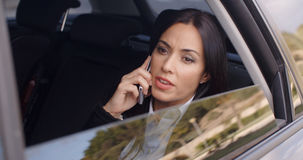 Serious female executive on phone in limousine Royalty Free Stock Photography