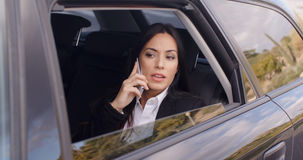 Serious female executive on phone in limousine Stock Image