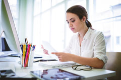 Serious female graphic designer reading document. At desk in creative office Royalty Free Stock Photo