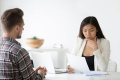 Serious Asian employer reading cv doubting in employees candidat. Serious female hr reading job candidates resume, thinking about candidature for open position stock image