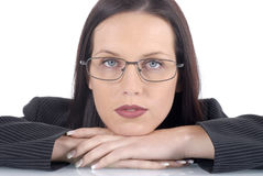 Serious female lawyer wearing suit and glasses, white background, arms on office desk Royalty Free Stock Photo