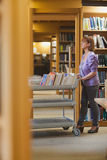 Serious female librarian pushing a cart Royalty Free Stock Images