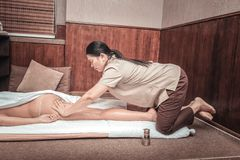 Serious female masseuse massaging her clients body. Focused on work. Serious female masseuse working with her hands while massaging her clients body royalty free stock photos