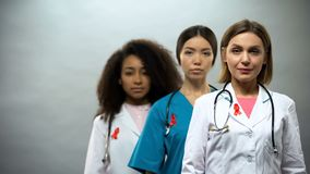 Serious female nurses with red ribbons looking into camera, AIDS awareness stock image
