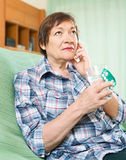 Serious female pensioner with pills and glass of water Royalty Free Stock Images