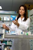 Serious female pharmacist working Stock Images
