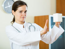 Serious female physician warning of faulty drugs Royalty Free Stock Photography
