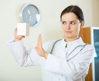 Serious female physician warning of faulty drugs Royalty Free Stock Photo