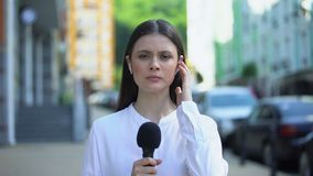 Serious female reporter with microphone in front of camera, breaking news