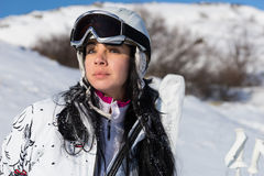 Serious female skier in front of ski equipment Royalty Free Stock Photo