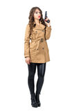 Serious female spy wearing beige coat holding gun looking at camera. Full body length portrait isolated over white studio background Royalty Free Stock Photography