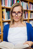 Serious female student reading a book in the library Royalty Free Stock Photo