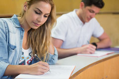 Serious female student writing during class Royalty Free Stock Photos