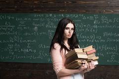 Free Serious Female Young Student Before Exams. Brunette Girl In Glasses Carrying Two Piles Of Heavy Books Stock Image - 128261331