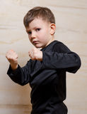 Serious Fighter Kid Posing with Closed Fists Stock Photo