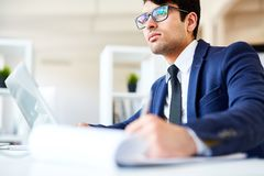 Pensive financier. Serious financier making online research of latest statistic data royalty free stock images