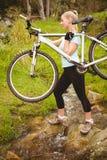 Serious fit woman lifting her bike Stock Photos