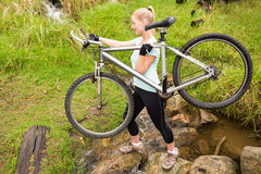 Serious fit woman lifting her bike Royalty Free Stock Image