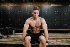 Serious fitness model of a bodybuilder male trainer sitting on a bench in the locker room. After or before training. On the background of a bag, a phone and a Stock Photography