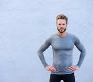 Serious fitness trainer standing against gray background Royalty Free Stock Photography