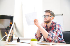 Serious focused designer looking and checking blueprint in office Stock Image