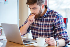 Serious focused man sitting at the table and using laptop Royalty Free Stock Photography