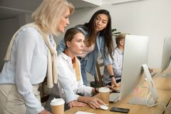 Serious focused multiracial female colleagues working together o royalty free stock image