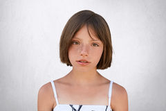 Serious freckled girl with bobbed hair and dark eyes looking directly into camera, isolated over white background. Stylish adorabl. E little girl in white dress royalty free stock image
