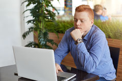 A serious freckled red head student wearing stylish checked shirt and watch sitting in cosy cafe keeping his hands on keyboard of Royalty Free Stock Images