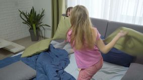 Serious friendly match. Happy friends having fun together. two girls fighting pillows stock video footage