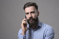 Serious frowning young bearded business man talking on the cell phone with intense look at camera Royalty Free Stock Photo