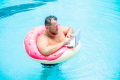 Serious Funny fat male in pink glasses on an inflatable circle in the pool works on a laptop portraying a girl. royalty free stock images