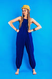 Serious funny woman in blue jumpsuit and straw hat Royalty Free Stock Images