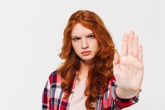 Serious ginger woman in shirt showing stop gesture at camera. Over gray background stock photos