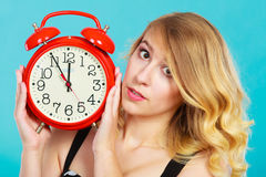 Serious girl with alarm clock on blue. Royalty Free Stock Photo