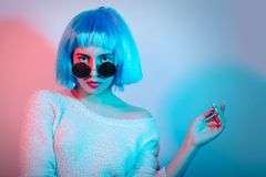 Girl in blue wig. Serious girl in blue wig on multicolor background Royalty Free Stock Images