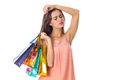 Serious girl closing her eyes holding a lot of bright packages isolated on white background Stock Images