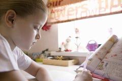 Serious Girl Doing Homework At Window Desk Stock Image