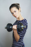 Serious girl with dumbbell Royalty Free Stock Images