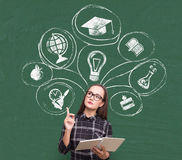 Serious girl and education choice icons. Portrait of a serious girl wearing glasses and a checkered shirt and standing near a green chalkboard with education Royalty Free Stock Photos